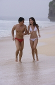 Couple running along beach - Asia Images Group
