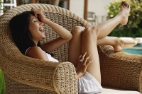 Young woman sitting on wicker chair, laughing - Asia Images Group