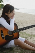Young woman sitting on beach, leaning on guitar - Asia Images Group