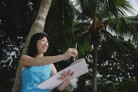 Woman with sketchbook standing under a coconut tree - Asia Images Group