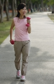 Mature woman using dumbbells, walking along path - Asia Images Group