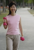 Mature woman using dumbbells in park - Asia Images Group