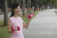 Mature woman exercising with dumbbells in park - Asia Images Group