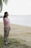Woman standing on beach, smiling - Asia Images Group