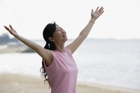 Woman standing on beach, looking up, arms outstretched - Asia Images Group