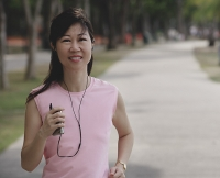 Mature woman walking in park, listening to MP3 player - Asia Images Group