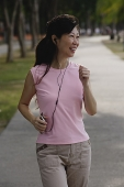 Mature woman walking in park, listening to MP3 player, smiling - Asia Images Group