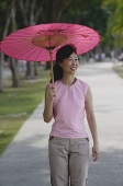 Mature woman walking in park, using pink umbrella - Asia Images Group