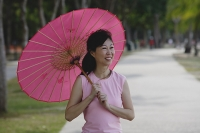 Mature woman using pink umbrella - Asia Images Group