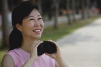 Mature woman holding binoculars, looking away - Asia Images Group
