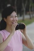 Mature woman holding binoculars - Asia Images Group