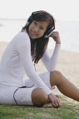 Young woman listening to music, wearing headphones - Asia Images Group
