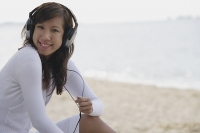 Young woman wearing headphones, smiling at camera - Asia Images Group
