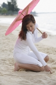 Young woman playing with sand on beach, holding pink umbrella - Asia Images Group