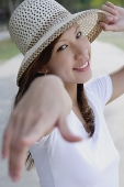 Young woman wearing hat, pointing finger at camera, selective focus - Asia Images Group