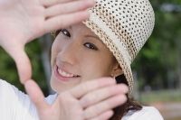 Young woman wearing hat, making finger frame - Asia Images Group