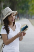 Young woman wearing hat, reading a book - Asia Images Group