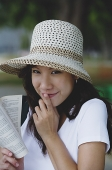 Young woman wearing hat, holding book, finger on mouth - Asia Images Group