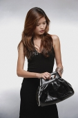 Woman in black dress, looking into black bag - Asia Images Group