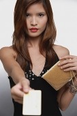 Woman in black top, holding out credit card - Asia Images Group