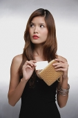 Woman in black top, putting credit card into purse - Asia Images Group