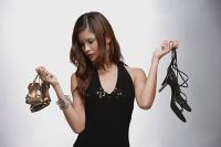 Woman in black top, holding two pairs of shoes - Asia Images Group
