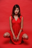 Woman in red dress, against red background - Asia Images Group
