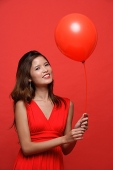 Woman in red dress, holding red balloon - Asia Images Group