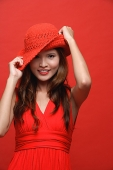 Woman in red dress with red hat against red background - Asia Images Group