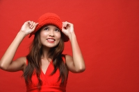 Woman in red dress with red hat against red background, smiling - Asia Images Group