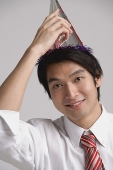 Businessman wearing party hat, looking at camera - Asia Images Group