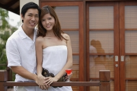 Couple standing side by side on balcony, smiling at camera - Asia Images Group