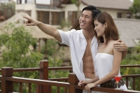 Couple standing side by side on balcony, man pointing, embracing woman - Asia Images Group