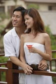 Couple standing side by side on balcony, smiling - Asia Images Group