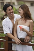 Couple standing side by side on balcony, smiling at each other - Asia Images Group