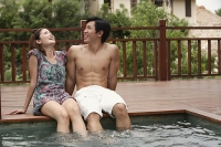 Couple sitting at the edge of swimming pool - Asia Images Group