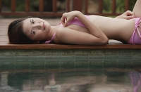 Woman lying down next to swimming pool, looking at camera - Asia Images Group