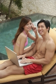 Couple sitting by swimming pool, man using laptop, woman on the phone, both smiling at camera - Asia Images Group
