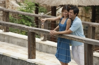 Couple standing side by side on bridge, woman pointing in the distance - Asia Images Group