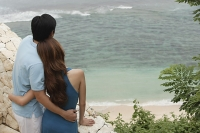 Couple standing side by side looking out at sea, rear view - Asia Images Group