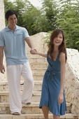 Couple walking down stairs, woman pulling man - Asia Images Group