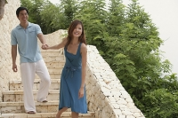 Couple walking down stairs, woman pulling man behind her - Asia Images Group