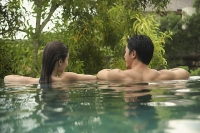 Couple in swimming pool, rearview - Asia Images Group
