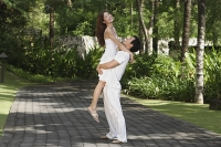 Couple in garden, man carrying woman - Asia Images Group