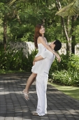 Couple in garden, man lifting woman up - Asia Images Group