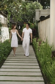 Couple walking along path in garden, holding hands - Asia Images Group