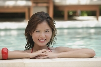 Woman at the edge of swimming pool, smiling - Asia Images Group