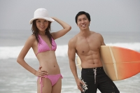 Couple on beach, man carrying surfboard - Asia Images Group