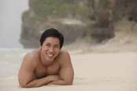 Man lying on beach, arms crossed - Asia Images Group
