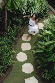 Young woman walking in tropical garden, smiling at camera - Asia Images Group